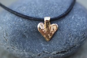 Jewelry made from recycled sterling silver and 14k gold on an organic cotton cord.